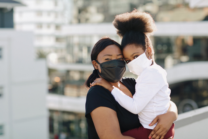 Mother holding daughter while wearing masks