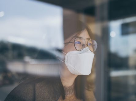 Woman with mask and glasses looking out a window